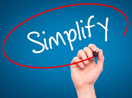 simplify: Man Hand writing Simplify with black marker on visual screen. Isolated on blue. Business, technology, internet concept. Stock Photo
