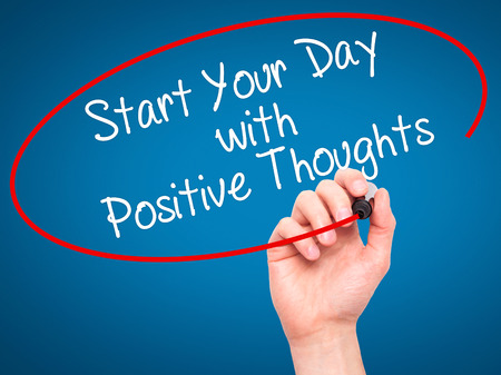 dat: Man Hand writing Start your Dat with Positive Thoughts with black marker on visual screen. Isolated on blue. Business, technology, internet concept. Stock Photo