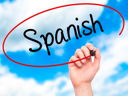 spaniard: Man Hand writing Spanish with black marker on visual screen. Isolated on background. Business, technology, internet concept. Stock Photo Stock Photo