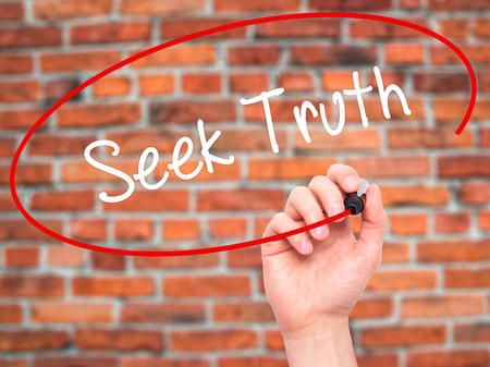 seek: Man Hand writing Seek Truth with black marker on visual screen. Isolated on bricks. Business, technology, internet concept.