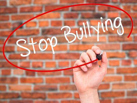 workplace harassment: Escritura de la mano del hombre Stop Bullying con marcador negro en la pantalla visual. Aislados en ladrillos. Negocios, la tecnología, el concepto de internet. Foto de stock