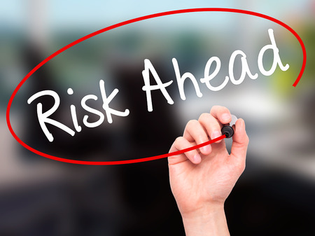 risk ahead: Man Hand writing Risk Ahead with black marker on visual screen. Isolated on office. Business, technology, internet concept. Stock Image