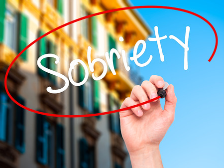 sobriety: Man Hand writing Sobriety with black marker on visual screen. Isolated on city. Business, technology, internet concept. Stock Photo