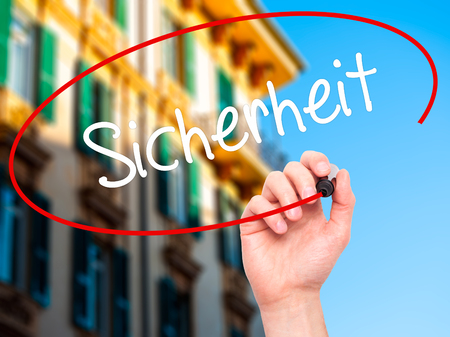 cautionary: Man Hand writing Sicherheit (Safety in German) with black marker on visual screen. Isolated on city. Business,  internet concept. Stock Photo