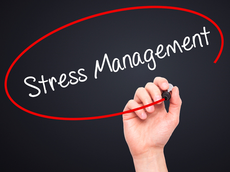 stressing: Man Hand writing Stress Management with black marker on visual screen. Isolated on black. Business, technology, internet concept. Stock Photo