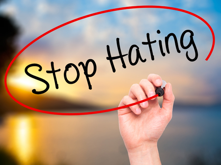 oppose: Man Hand writing Stop Hating  with black marker on visual screen. Isolated on background. Business, technology, internet concept. Stock Photo Stock Photo