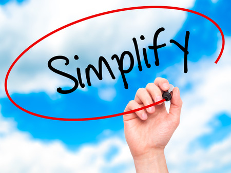 simplify: Man Hand writing Simplify with black marker on visual screen. Isolated on sky. Business, technology, internet concept. Stock Photo