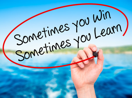 capable of learning: Man Hand writing Sometimes you Win Sometimes you Learn  with black marker on visual screen. Isolated on nature. Business, technology, internet concept. Stock Photo
