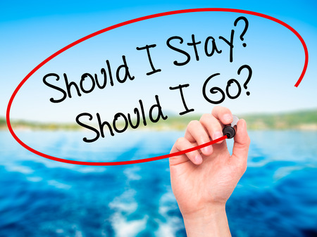indecisiveness: Man Hand writing Should I Stay? Should I Go? with black marker on visual screen. Isolated on nature. Business, technology, internet concept. Stock Photo Stock Photo
