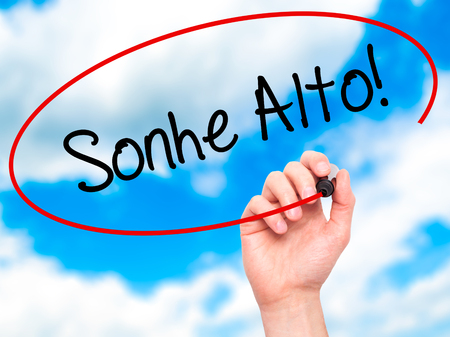 Man Hand writing Sonhe Alto! (Dream Big in Portuguese) with black marker on visual screen. Isolated on sky. Business, technology, internet concept. Stock Photo