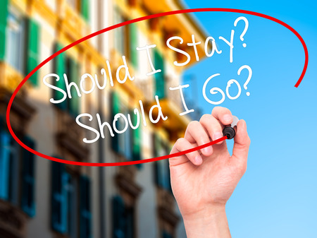 indecisiveness: Man Hand writing Should I Stay? Should I Go? with black marker on visual screen. Isolated on city. Business, technology, internet concept. Stock Photo Stock Photo