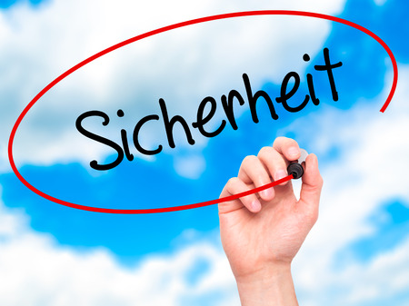 sicherheit: Man Hand writing Sicherheit (Safety in German) with black marker on visual screen. Isolated on sky. Business,  internet concept. Stock Photo Stock Photo