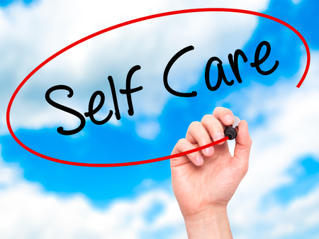 Man Hand writing Self Care with black marker on visual screen. Isolated on background. Business, technology, internet concept. Stock Photo