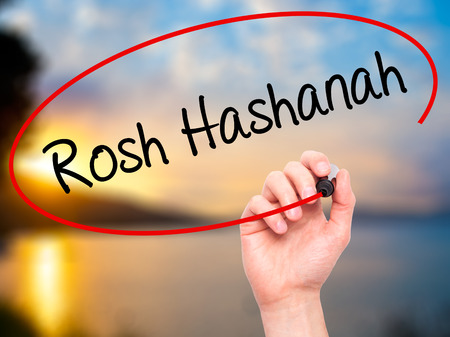 24 26: Man Hand writing Rosh Hashanah with black marker on visual screen. Isolated on nature. Business, technology, internet concept. Stock Photo