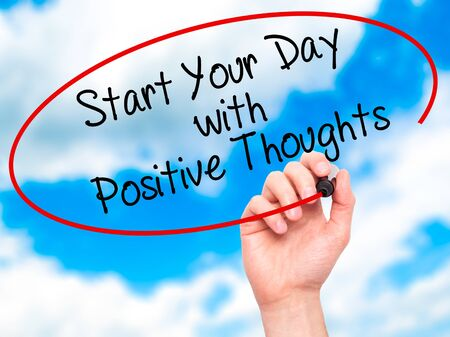 positiveness: Man Hand writing Start your Dat with Positive Thoughts with black marker on visual screen. Isolated on sky. Business, technology, internet concept. Stock Photo Stock Photo