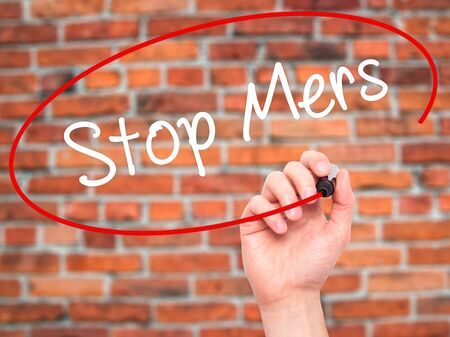 coronavirus: Man Hand writing Stop Mers with black marker on visual screen. Isolated on background. Business, technology, internet concept. Stock Photo Stock Photo