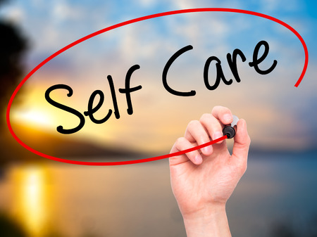 self care: Man Hand writing Self Care with black marker on visual screen. Isolated on background. Business, technology, internet concept. Stock Photo