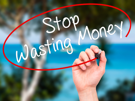corporate waste: Man Hand writing Stop Wasting Money with black marker on visual screen. Isolated on nature. Business, technology, internet concept. Stock Photo