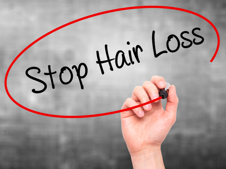 Healthy hair: Man Hand writing Stop Hair Loss  with black marker on visual screen. Isolated on grey. Business, technology, internet concept. Stock Photo