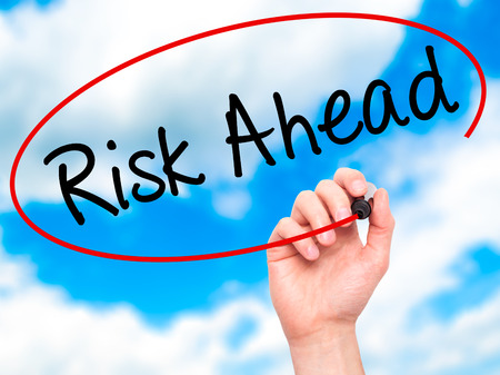 risk ahead: Man Hand writing Risk Ahead with black marker on visual screen. Isolated on sky. Business, technology, internet concept. Stock Image