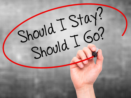 indecisiveness: Man Hand writing Should I Stay? Should I Go? with black marker on visual screen. Isolated on grey. Business, technology, internet concept. Stock Photo