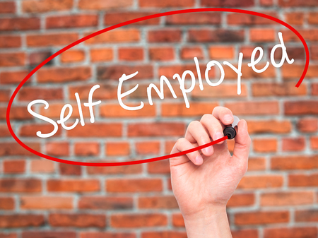 self employed: Man Hand writing Self Employed with black marker on visual screen. Isolated on bricks. Business, technology, internet concept. Stock Photo