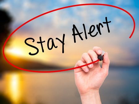 stay alert: Man Hand writing Stay Alert with black marker on visual screen. Isolated on nature. Business, technology, internet concept. Stock Photo