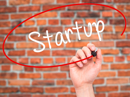 self starter: Man Hand writing Startup  with black marker on visual screen. Isolated on bricks. Business, technology, internet concept. Stock Photo