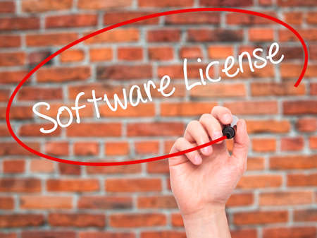 linker: Man Hand writing Software License with black marker on visual screen. Isolated on bricks. Business, technology, internet concept. Stock Photo