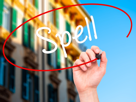 grammatical: Man Hand writing Spell with black marker on visual screen. Isolated on city. Business, technology, internet concept. Stock Photo