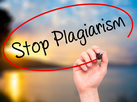 plagiarism: Man Hand writing Stop Plagiarism with black marker on visual screen. Isolated on background. Business, technology, internet concept. Stock Photo