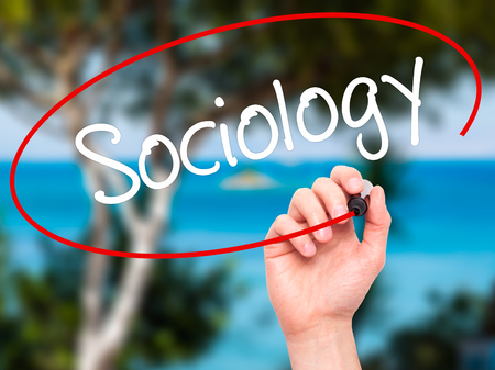 sociologia: Hombre de la mano escribiendo Sociolog�a con marcador negro en la pantalla visual. Aislado en el fondo. Negocios, la tecnolog�a, el concepto de internet. Foto de stock