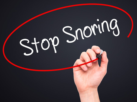 snore: Man Hand writing Stop Snoring with black marker on visual screen. Isolated on black. Business, technology, internet concept. Stock Photo Stock Photo