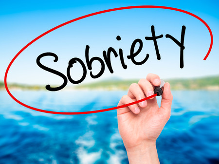 sobriety: Man Hand writing Sobriety with black marker on visual screen. Isolated on nature. Business, technology, internet concept. Stock Photo Stock Photo