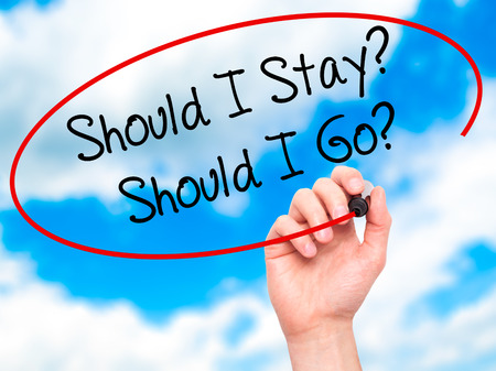 indecisiveness: Man Hand writing Should I Stay? Should I Go? with black marker on visual screen. Isolated on sky. Business, technology, internet concept. Stock Photo