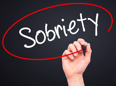 sobriety: Man Hand writing Sobriety with black marker on visual screen. Isolated on black. Business, technology, internet concept. Stock Photo