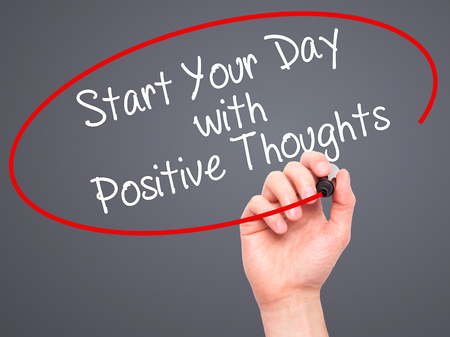 positiveness: Man Hand writing Start your Dat with Positive Thoughts with black marker on visual screen. Isolated on grey. Business, technology, internet concept. Stock Photo Stock Photo