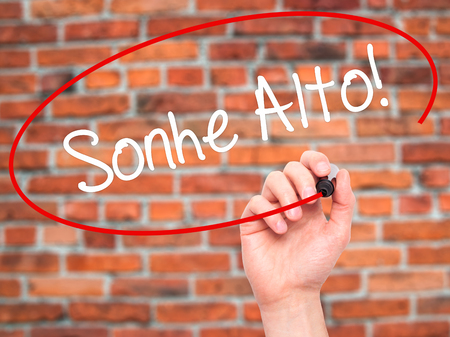 Man Hand writing Sonhe Alto! (Dream Big in Portuguese) with black marker on visual screen. Isolated on bricks. Business, technology, internet concept. Stock Photo