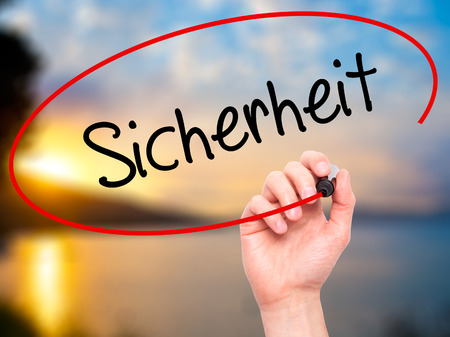 sicherheit: Man Hand writing Sicherheit (Safety in German) with black marker on visual screen. Isolated on nature. Business,  internet concept. Stock Photo