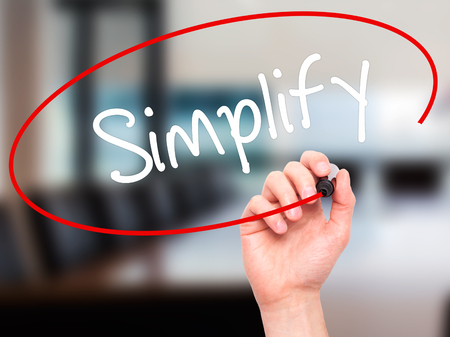 simplify: Man Hand writing Simplify with black marker on visual screen. Isolated on office. Business, technology, internet concept. Stock Photo Stock Photo
