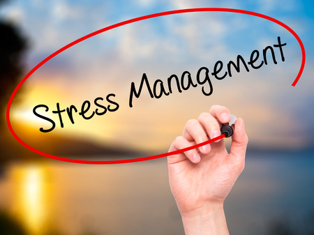 stressing: Man Hand writing Stress Management with black marker on visual screen. Isolated on nature. Business, technology, internet concept. Stock Photo