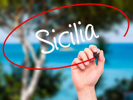 ner: Man Hand writing Sicilia (Sicily In Italian)  with black marker on visual screen. Isolated on nature. Business, technology, internet concept. Stock Photo