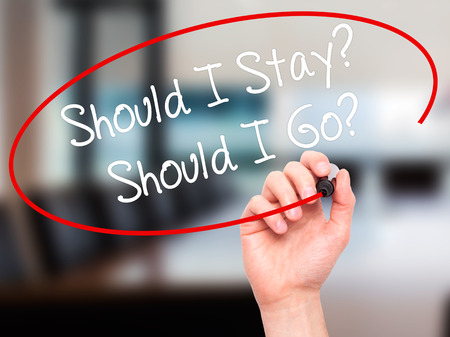 indecisiveness: Man Hand writing Should I Stay? Should I Go? with black marker on visual screen. Isolated on office. Business, technology, internet concept. Stock Photo Stock Photo