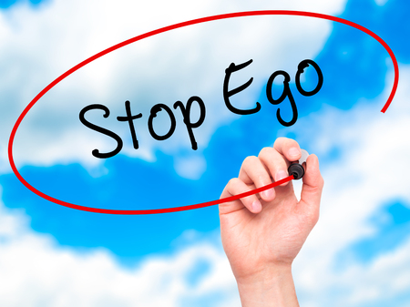 egoist: Man Hand writing  Stop Ego with black marker on visual screen. Isolated on background. Business, technology, internet concept. Stock Photo