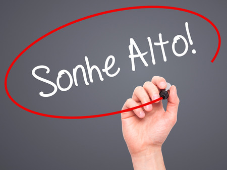 Man Hand writing Sonhe Alto! (Dream Big in Portuguese) with black marker on visual screen. Isolated on grey. Business, technology, internet concept. Stock Photo