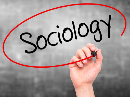 Man Hand writing Sociology  with black marker on visual screen. Isolated on background. Business, technology, internet concept. Stock Photo