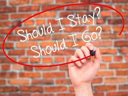 indecisiveness: Man Hand writing Should I Stay? Should I Go? with black marker on visual screen. Isolated on bricks. Business, technology, internet concept. Stock Photo Stock Photo