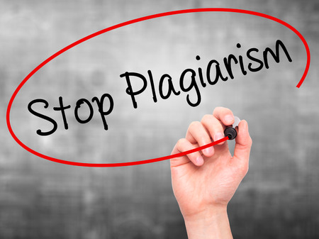 copycat: Man Hand writing Stop Plagiarism with black marker on visual screen. Isolated on background. Business, technology, internet concept. Stock Photo