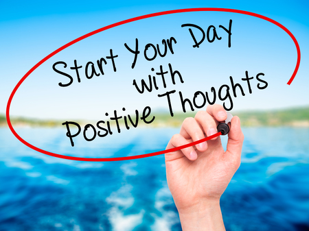 positiveness: Man Hand writing Start your Dat with Positive Thoughts with black marker on visual screen. Isolated on nature. Business, technology, internet concept. Stock Photo