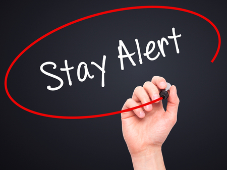 safety first: Man Hand writing Stay Alert with black marker on visual screen. Isolated on black. Business, technology, internet concept. Stock Photo